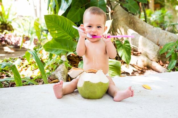 Glückliches säuglingsbaby im tropischen urlaub isst und trinkt grüne junge kokosnuss sitzt auf dem boden