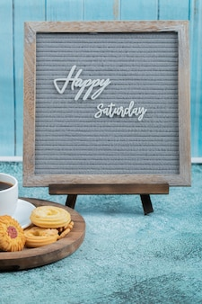Glückliches samstagsplakat mit keksen und einer tasse getränk