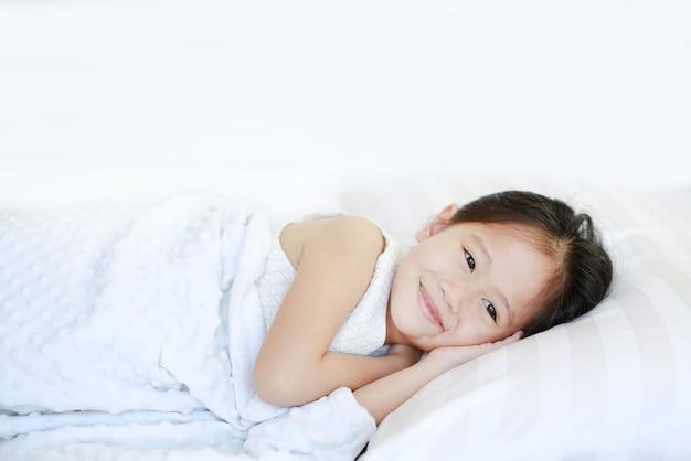 Glückliches schlafendes schönes asiatisches kindermädchen, das auf bett liegt.