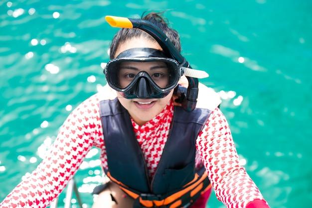 Glückliches schnorchelmädchen, das spaß im ozeanwasserschnorcheln auf karibikurlaub in thailand hat