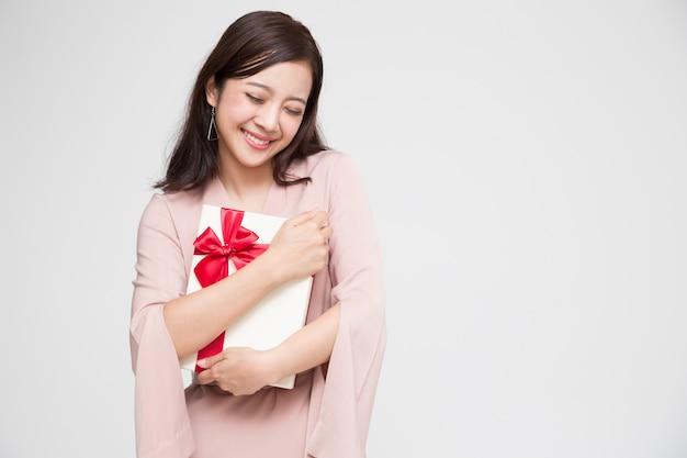 Glückliches schönes asiatisches frauenlächeln mit roter geschenkbox. verliebte teenager, geschenke von liebhabern empfangend. neujahr, weihnachten und valentinstag-konzept