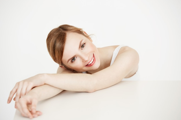 Glückliches schönes blondes mädchen mit der gesunden sauberen haut lächelnd am tisch sitzen. gesichtsbehandlung.