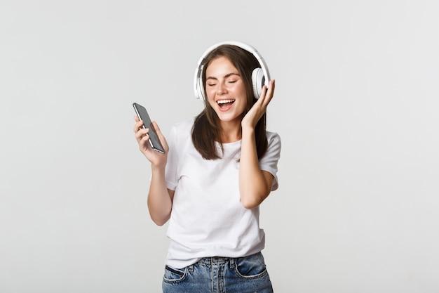 Glückliches schönes brünettes mädchen tanzt und hört musik in kabellosen kopfhörern, hält smartphone.