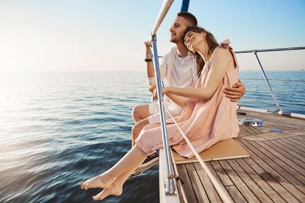 Glückliches schönes erwachsenes paar, das auf seite der yacht sitzt, am meer zuschaut und im urlaub umarmt. tan mag verblassen, aber solche erinnerungen, die sie mit einem teilen, den sie lieben, halten ewig an