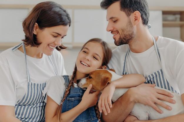 Glückliches schönes familienlächeln und aufrichtige gefühle ausdrücken, genießen sie zeit zusammen in gemütlichem zuhause zu verbringen.