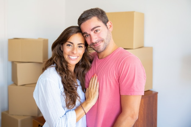 Glückliches schönes hispanisches paar, das zwischen kartonschachteln in ihrer neuen wohnung steht, umarmt und kamera betrachtet