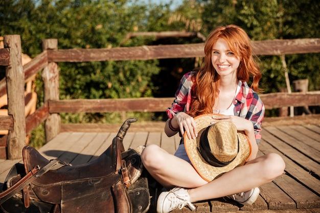 Glückliches schönes junges frauengowgirl mit hut, der auf ranch sitzt