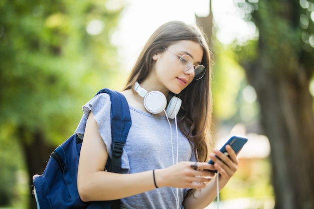 Glückliches schönes junges kaukasisches mädchen mit grünem smartphone draußen am sonnigen sommertag, der sms schreibt und lächelt.