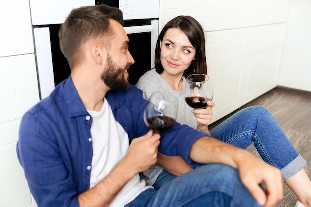 Glückliches schönes junges paar in lässigen outfits, die auf boden sitzen und rotwein trinken, während jubiläum zu hause feiern