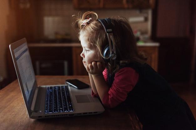 Glückliches schönes kind in den kopfhörern, die musik hören