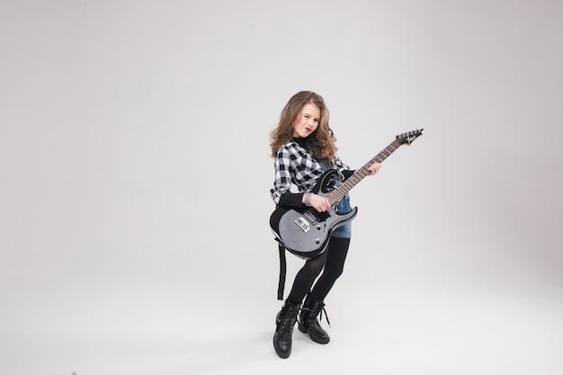 Glückliches schönes künstlerisches kleines mädchen, das gitarre spielt
