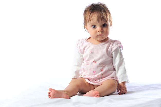 Glückliches schönes lächelndes einjähriges baby, das mit lätzchenporträt sitzt