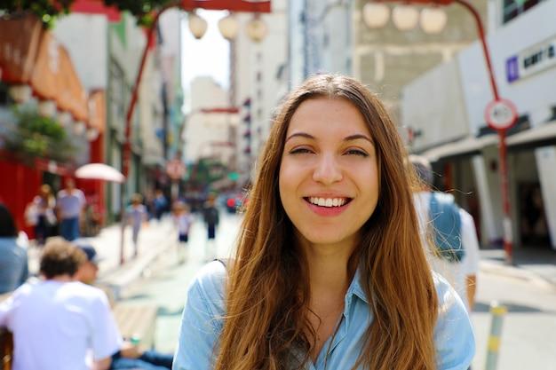 Glückliches schönes lächelndes mädchen, das in der japanischen nachbarschaft liberdade sao paulo, sao paulo, brasilien geht