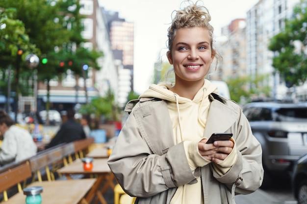 Glückliches schönes mädchen, das auf jemanden außerhalb des cafés wartet, handy hält und lächelt.