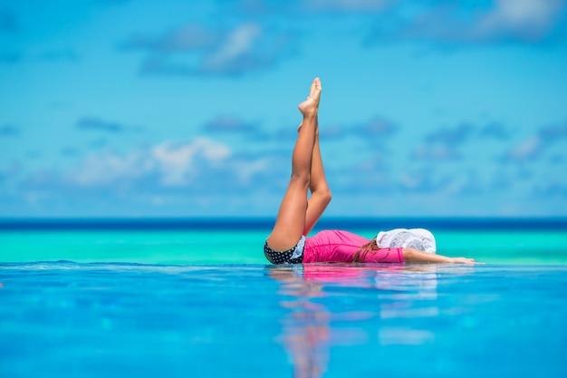 Glückliches schönes mädchen, das spaß swimmingpool im im freien hat