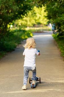 Glückliches schönes mädchen fährt im sommer an einem windigen tag auf dem tretroller die straße entlang