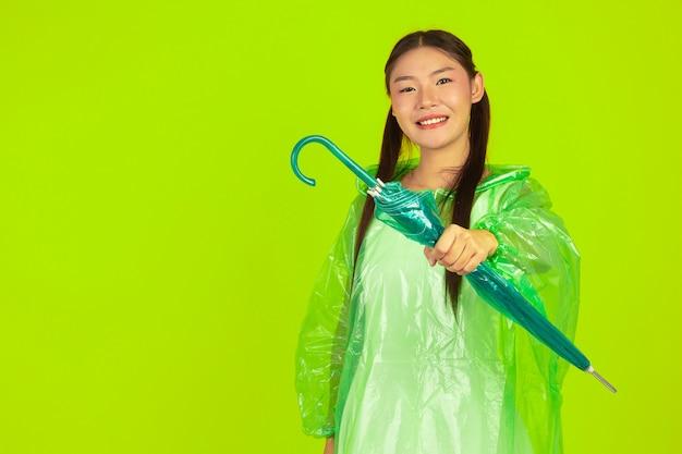 Glückliches schönes mädchen, grüne kleidung, regenschirm und mantel, regnerischer tag tragend.