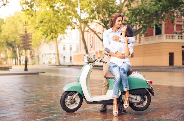 Glückliches schönes paar auf roller in der alten europäischen stadt