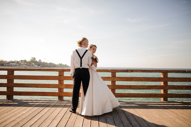 Glückliches schönes paar, das auf dem hölzernen pier am see steht. vorstellung der hochzeit