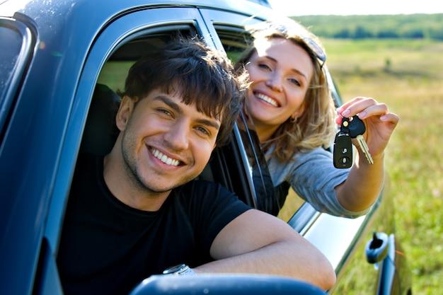 Glückliches schönes paar, das die schlüssel zeigt, die im neuen auto sitzen