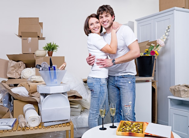 Glückliches schönes paar, das in ihrer neuen wohnung umarmt