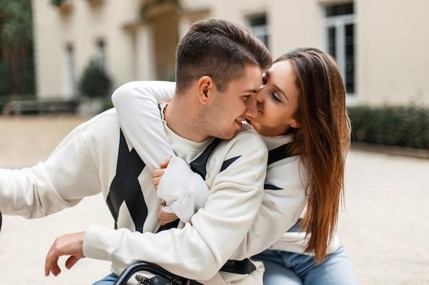 Glückliches schönes paar in den weißen pullovern, die draußen umarmen