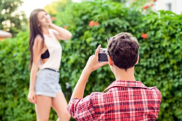 Glückliches schönes paar nahe grüner wand im lässigen stil mit kamera