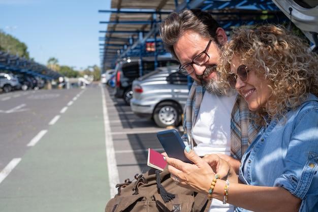 Glückliches schönes paar reisende, die pass halten und handy benutzen. sitzen auf dem parkplatz und warten auf call boarding