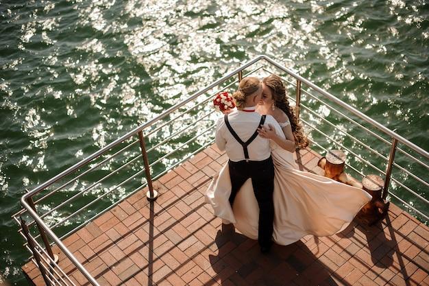 Glückliches schönes paar tanzt auf dem holzsteg am see. vorstellung der hochzeit