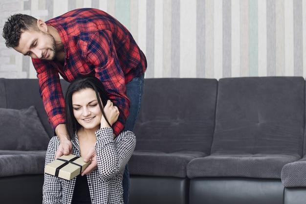 Glückliches schönes paar zusammen zu hause, ein mann gibt einer frau ein geschenk für den urlaub