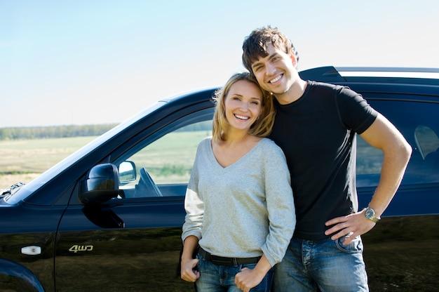 Glückliches schönes schönes paar, das nahe dem auto steht