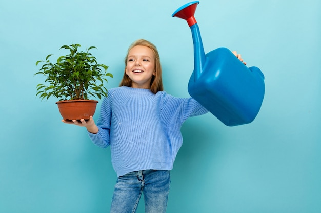 Glückliches schönes schulmädchen kümmert sich um einer anlage mit einer gießkanne für die bewässerung von blumen auf einem blauen hintergrund