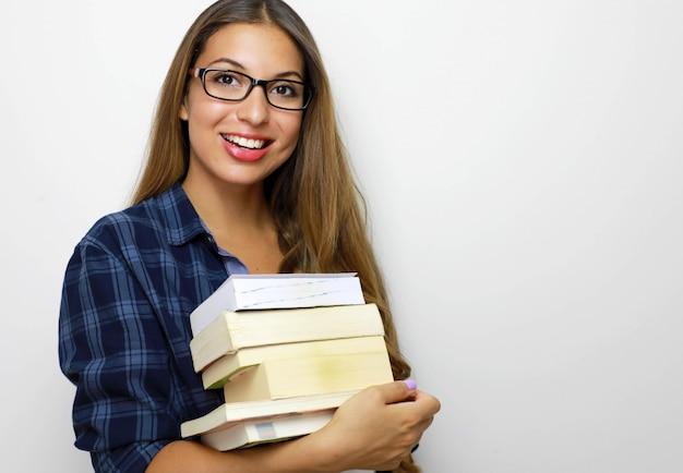Glückliches schönes studentenmädchen mit brille und stapel bücher in ihren händen