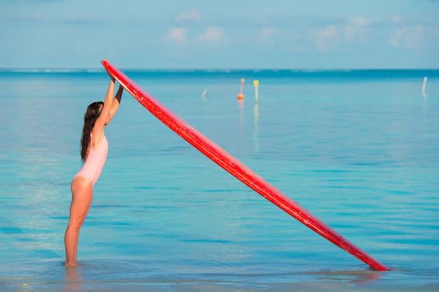 Glückliches schönes surfermädchen am strand mit ihrem surfbrett