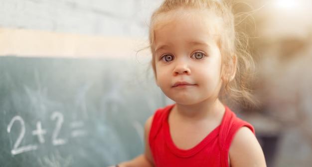 Glückliches schulmädchen auf matheklassen im kindergarten, der lösung findet und probleme löst