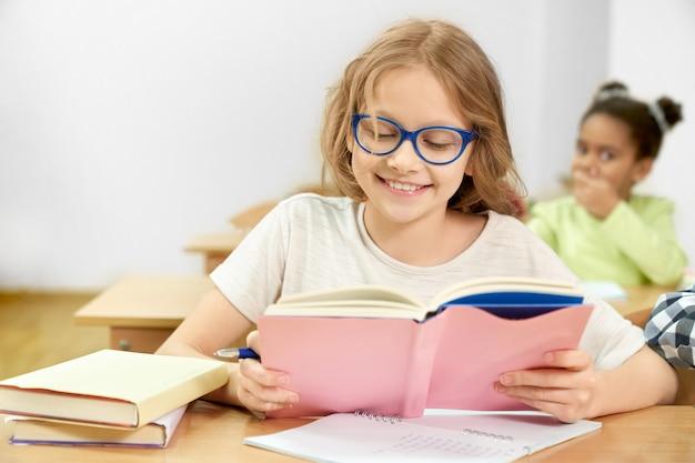 Glückliches schulmädchen, das am schreibtisch studiert und im buch schaut und lächelt.