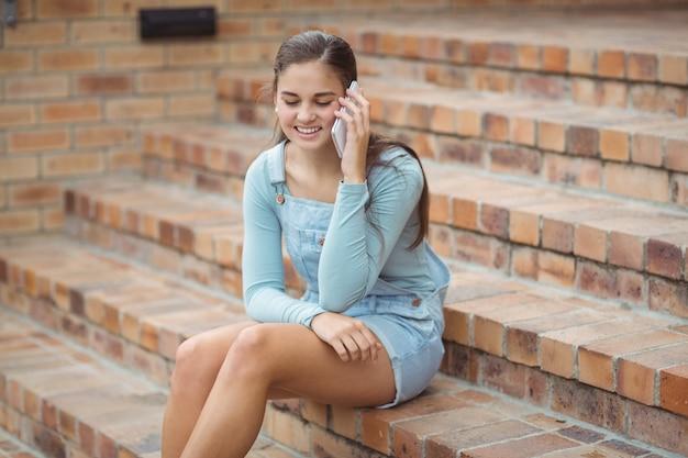 Glückliches schulmädchen, das auf treppe sitzt und handy spricht