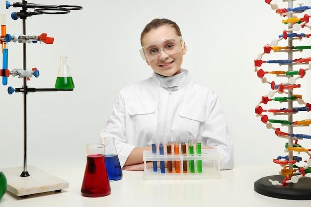 Glückliches schulmädchen im chemieunterricht auf hellem hintergrund