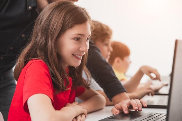 Glückliches schulmädchen mit lehrer, der laptop während des unterrichts verwendet