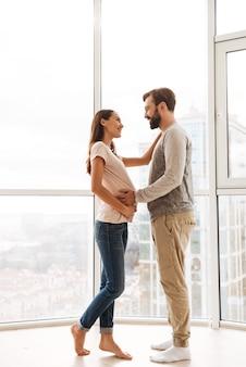 Glückliches schwangeres junges paar, das umarmt
