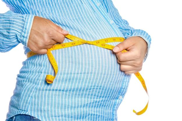 Glückliches schwangeres mädchen liegt auf weißem hintergrund