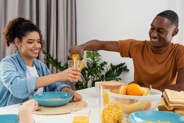 Glückliches schwarzes familienpaar, das saft trinkt
