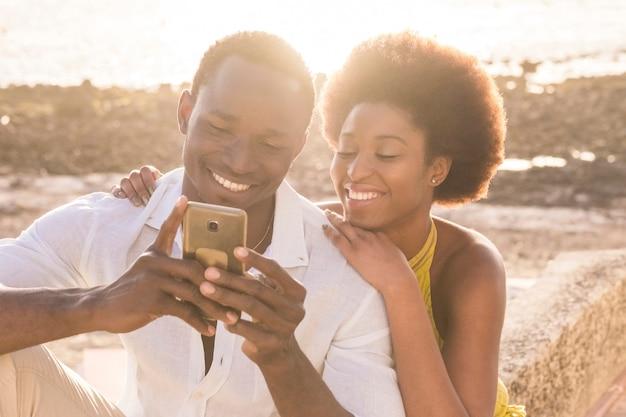 Glückliches schwarzes junges paar am strand mit hintergrundbeleuchtung des sonnenuntergangs auf der oberfläche, lächeln und lachen mit einem smartphone, um mit freunden zu chatten oder bilder des urlaubs zu sehen