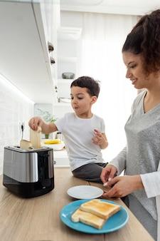 Glückliches schwarzes kind, das seiner mutter beim frühstück hilft