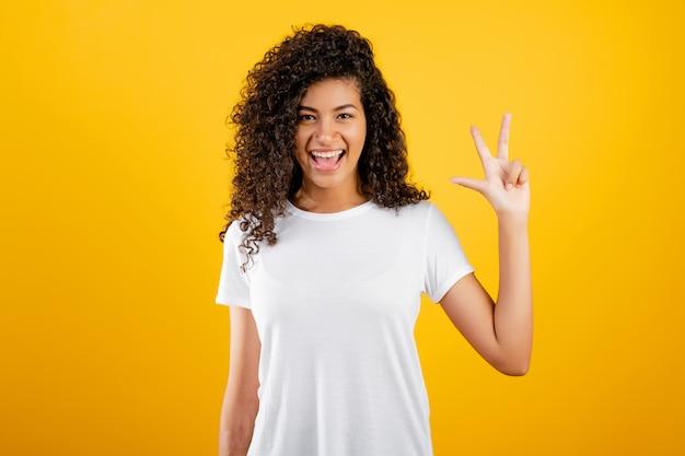 Glückliches schwarzes mädchen, das drei finger getrennt über gelb zeigt