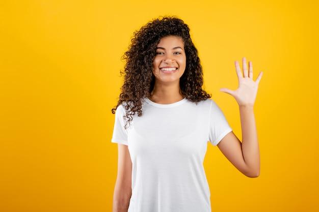 Glückliches schwarzes mädchen, das fünf finger getrennt über gelb zeigt