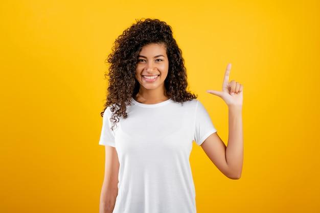 Glückliches schwarzes mädchen, das zwei finger getrennt über gelb zeigt