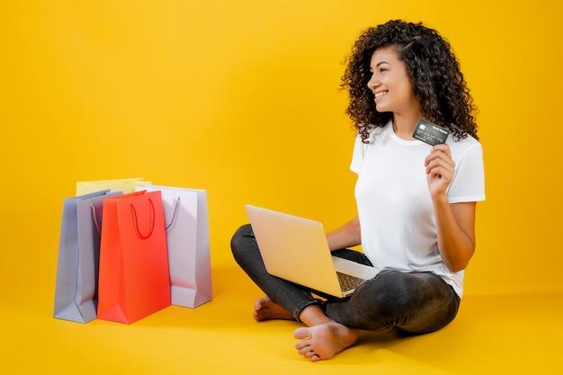 Glückliches schwarzes mädchen mit den bunten einkaufstaschen, die mit dem laptop und kreditkarte lokalisiert über gelb sitzen