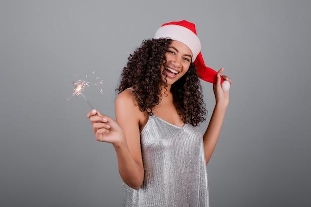 Glückliches schwarzes mädchen mit den funkelnden wunderkerzen, die den weihnachtshut und -kleid lokalisiert über grau tragen