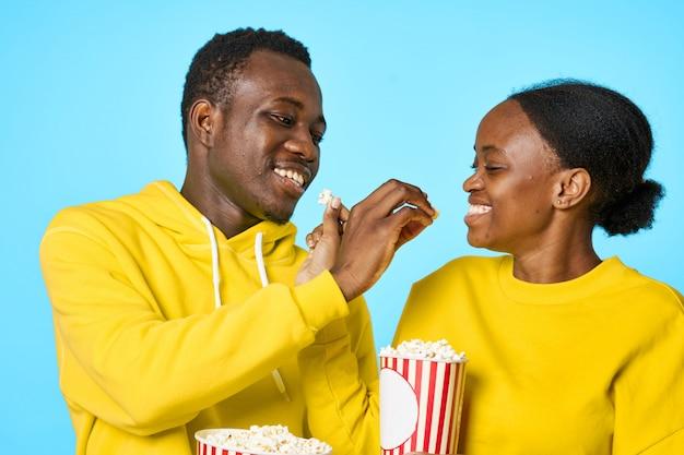 Glückliches schwarzes paar, das popcorn isst und film sieht